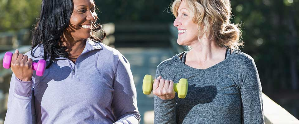 Two energetic women smile at each other in the park while lifting small weights.