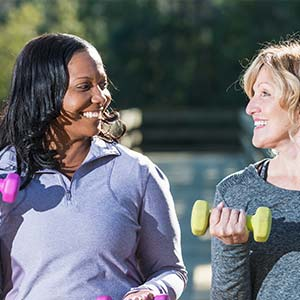 Two women smile at each other in the park while lifting small weights.