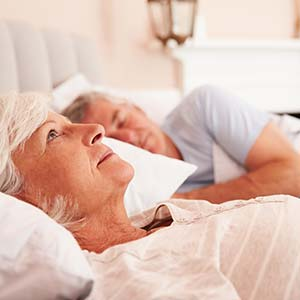 An elderly woman lies in bed and stares at the ceiling while her partner sleeps peacefully beside her.