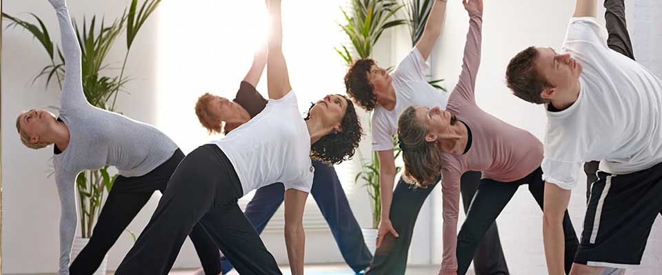 A group of athletic coworkers participate in a calming yoga class.