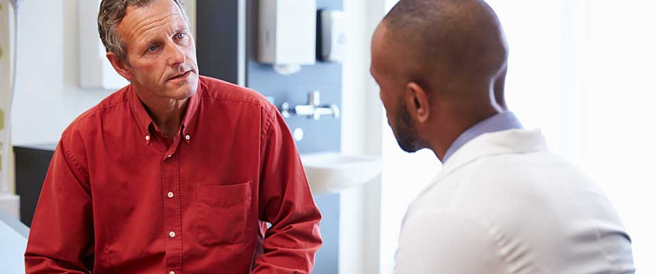 A man in a red button-up shirt discusses his health with his primary care doctor.