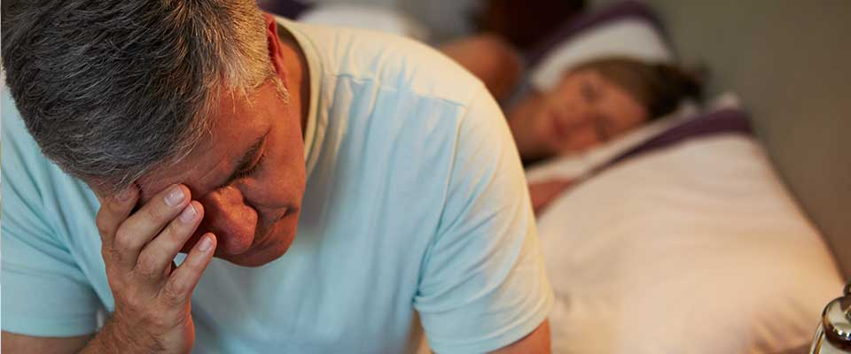 Man suffering from chronic insomnia sits on the edge of his bed, rubbing his head while his wife sleeps behind him.