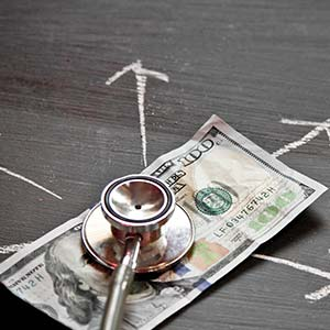 A stethoscope listens to a hundred dollar bill.