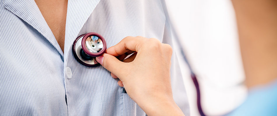 A doctor at a Centers of Excellence-approved facility listens to her patient's heartbeat with a stethoscope.