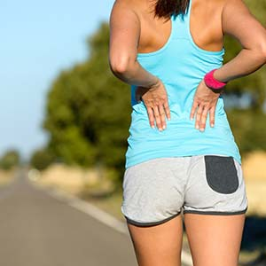 A female runner stops by the side of the road and stretches her lower back.