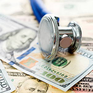 A stethoscope lies across a one hundred dollar bill.
