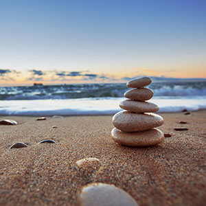 Stress management comes easy to a stack of flat rocks that stands peacefully on an ocean beach while waves crash in the background.