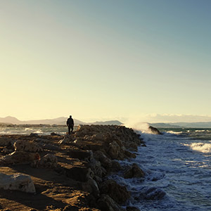 A man walks to the sea on the breakwater during sunset, to relieve his physical symptoms of stress.