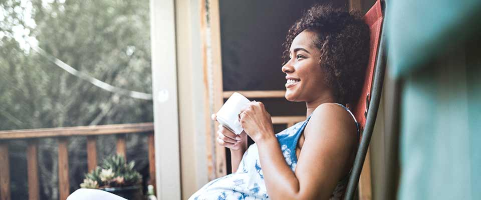 A pregnant woman relaxes on her back porch, smiling and sipping her tea.