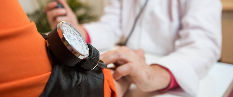 A doctor measures his patient's blood pressure, as part of a company's biometric screening initiative.