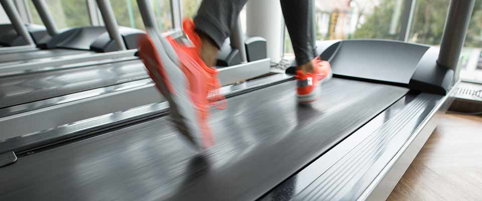 A woman in a blurred photograph runs on a treadmill, hitting her daily HIIT goals.