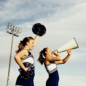 Two young cheerleaders at a high school game show their support with pom poms and a microphone.