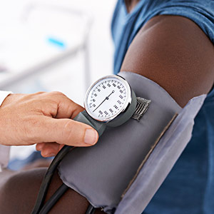 A doctor measures the blood pressure of a man in a blue short-sleeve shirt, in accordance with the new blood pressure guidelines from the American Heart Association.